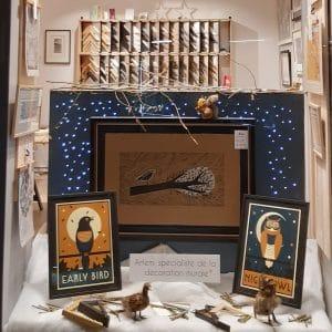 Vitrine de Noël de la boutique Artem rue Franklin à Nantes avec des affiches d'art encadrées, des lumières, des petits animaux pour décorer, des affiches suspendues sur des cintres