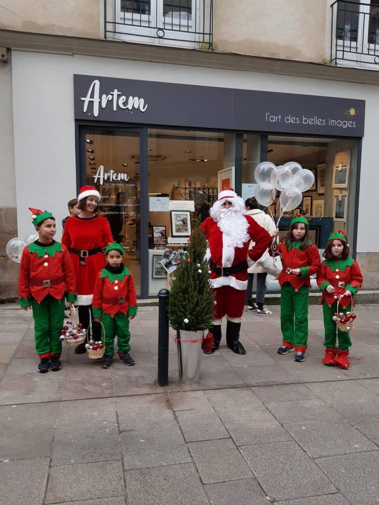 Mère Noël, Père Noël et leurs lutins sont devant la boutique Artem au 16 rue Franklin à Nantes. Ils offrent des ballons, des bonbons et des chocolats pour fêter Noël. Il y a un sapin de Noël dans un pot métallique avec un nœud rouge.