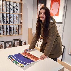 """Cécile Aurégan signe ses illustrations en série limitée, imprimée d'après ses peintures originales, pour la boutique Artem Nantes. On voit son illustration """"Le Chat de Tanger"""". Derrière l'artiste, les échantillons de baguettes pour l'encadrement sur-mesure des tableaux, une illustration de Mathilde Crétier, une sérigraphie de HelloMarine, une gravure de Cathie Pavoine, des exemples de cadres avec l'éléphant de Nantes."""
